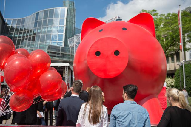 Spectators look on as the 'world's largest piggy bank' is being unveiled during a ceremony at Schillerplatz in Ludwigsburg, Germany, 18 May 2015. The two-story tall piggy bank was designed to motivate people to save money. http://time.com/money/4018927/guinness-world-records-money/